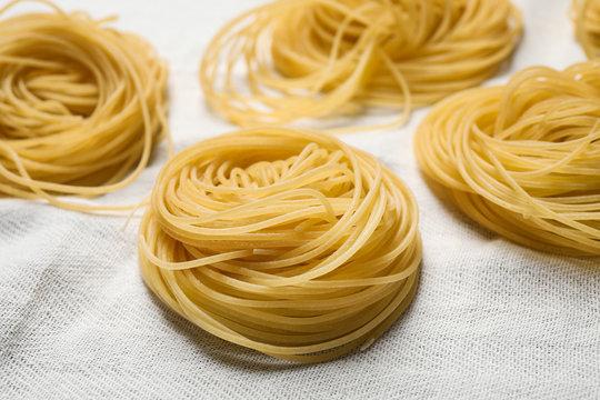Capellini pasta on white tablecloth, closeup view