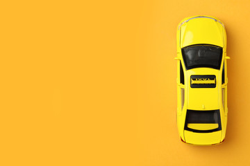 Yellow taxi car model on orange background, top view. Space for text