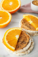 Puffed rice cakes with peanut butter and orange on white table