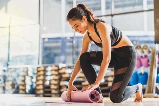 Asian Young woman rolling and unrolling yoga mat before and after practiced yoga sport, preparing for healthy or Meditation Exercise, wearing sportswear bra and pants, sports and healthcare concept