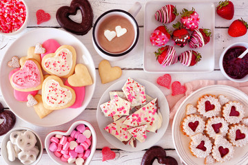 Valentines Day table scene with a selection of sweets and cookies. Top view over a white wood...