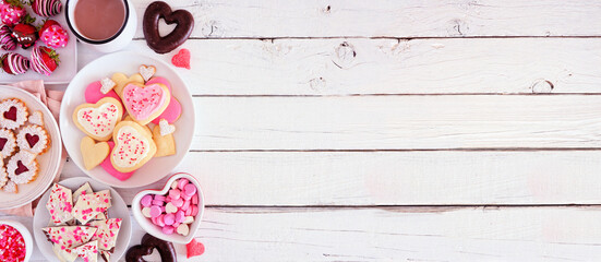 Valentines Day banner with side border of various sweets and cookies. Top view over a white wood...