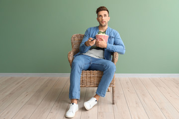 Handsome man watching movie while sitting in armchair near color wall