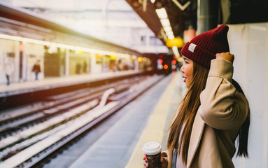 Fotomurales - young woman in train station travel concept background vintage tone.