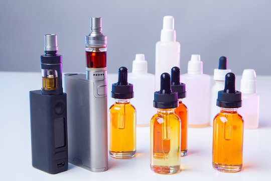 Vapes, liquids and white vials on the table. Smoking concept. Smoking electronic cigarettes. VAPE shop. Vaping. Vaper accessories.