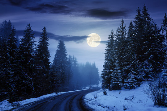 country road through forest at night. misty winter weather in full moon light. snow on the roadside. cloudy sky