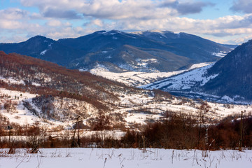 mountainous rural landscape on a sunny winter day. snow covered fields on hills. village in the distant valley. landscape with clouds on the sky
