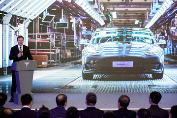 Tesla Inc CEO Elon Musk speaks next to a screen showing an image of Tesla Model 3 car during an opening ceremony for Tesla China-made Model Y program in Shanghai