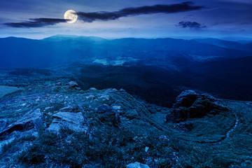mountain landscape in summer at night. view from the top of carpathian watershed ridge in to the distance in full moon light. boulders on the grassy slopes. weather with clouds on the dark sky