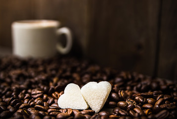 Many coffee beans. Coffee background. Two hearts of their sugar.