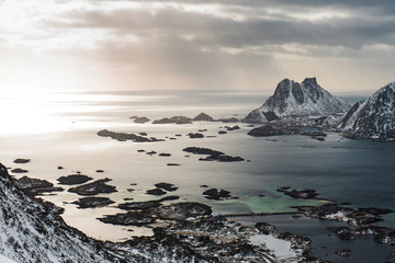 View of a landscape of a Norwegian fjord with a snowy mountain and rocks, Lofoten Islands