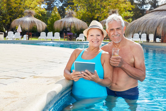 Seniors with tablet in the swimming pool