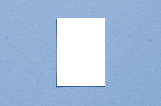 Blank white vertical paper sheet 5x7 inches with shadow overlay. Modern and stylish greeting card or wedding invitation mock up. Color of the year 2020 classic blue.