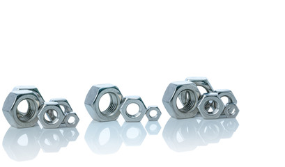 Set of metal hexagon nuts isolated on white background. Small, medium, and big of silver metal hexagon nuts. Hardware tool. Fastener with a threaded hole. Pattern of metal nuts with copy space.