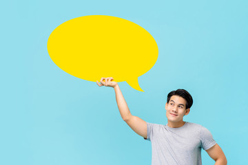 Smiling Asian man thinking and looking at speech bubble