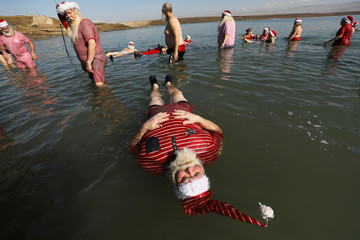A man, part of a group of trained Santa Clauses from various countries, wears a Santa Claus-themed bathing suit as he floats in the Dead Sea, at Neve Midbar beach in the Israeli-occupied West Bank