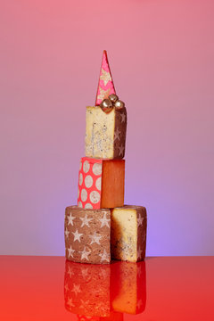 Stack of decorated cheese on an isolated pink purple background