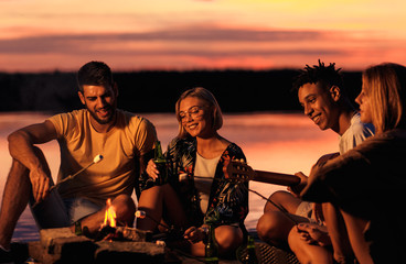 Group of young friends enjoying at the lake at night. They sitting around the fire singing and having fun at camping.