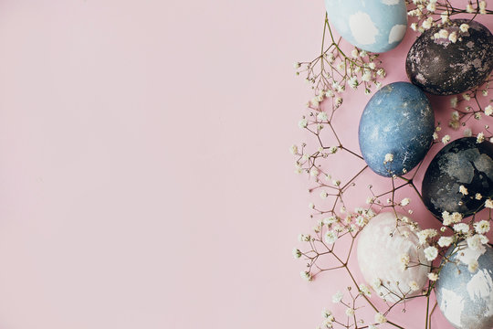 Stylish easter eggs and spring flowers border on pink paper flat lay, space for text. Modern natural dyed blue and marble easter eggs. Happy Easter. Greeting card template