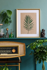 Interior design of living room with gold mock up photo frame on the green shelf with beautiful...