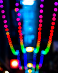 Rows of defocused illuminated globes under the marquee as is often used at the entrance to theatres, or city laneways