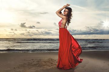 Stunning woman wearing beautiful red dress on the beach