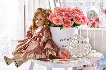 vintage style picture with bunch of pink roses and old doll