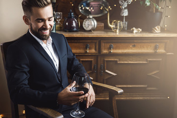 Handsome bearded man with a glass of red wine