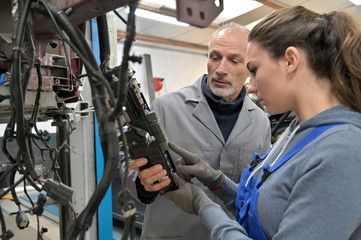 Trainee with mechanics manager working on car technology