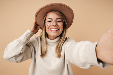 Portrait of cheerful young woman smiling and taking selfie photo