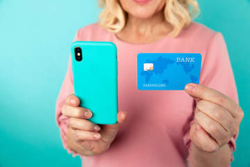 Closeup picture of cherrful female with phone and credit card isolated