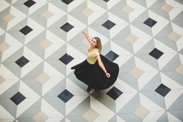 Woman young adult beautiful happy in a large hall with a floor with geometric tiles top view