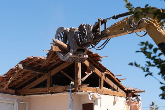 industrial excavator working demolition of house old residential building
