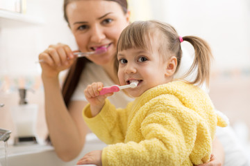 Smiling child girl with her mom brushing and clean teeth in bathroom