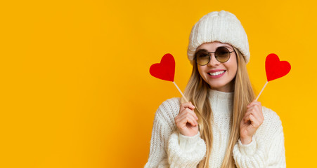 Attractive cheerful girl in knitted hat with valentine cards