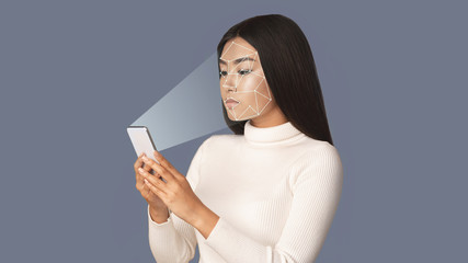 Spoed Foto op Canvas Hoogte schaal Biometric verification. Girl with smartphone using face ID