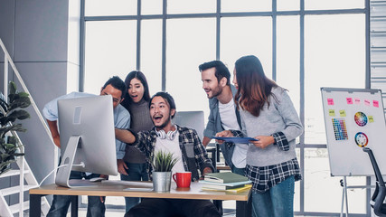 creative man designer point at desktop computer screen and tell colleague about good news of project success with glad at modern office