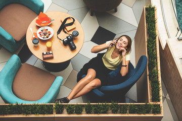 Woman young adult beautiful happy businesswoman sitting at a table in a restaurant for lunch top view