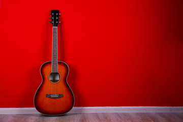 Cropped image of vintage style travel size acoustic guitar with rosewood neck and no pickguard over festive red wall background. Close up, copy space for text, top view. Wall mural