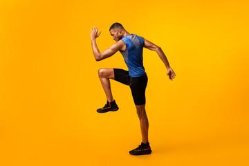 Young black sportsman walks highly lifting knees Fotobehang