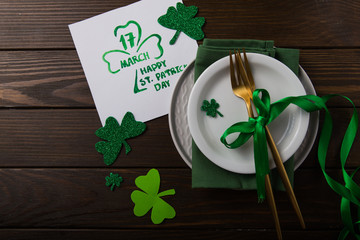 St Patrick's Day party table setting decorated with green leprechaun on wooden background.