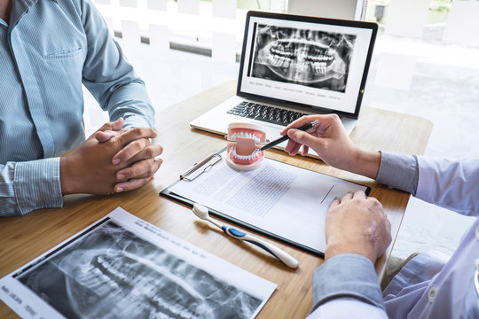 Professional Dentist showing  jaw and teeth the x-ray photograph and discussing during explaining the consultation treatment issues with patient and writing history list on report