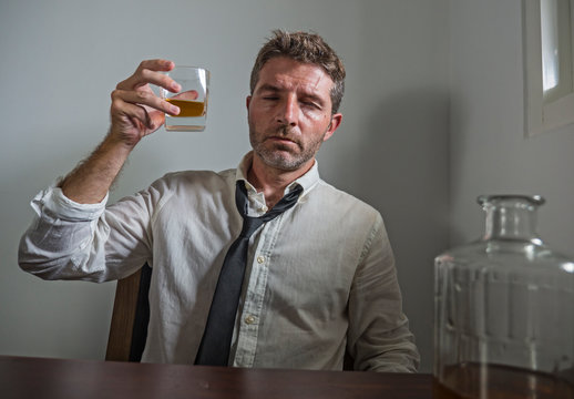 portrait of 30s to 40s alcoholic  man in lose necktie drinking desperate holding whiskey glass thoughtful drunk and depressed completely wasted in alcohol addiction concept