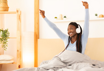 Wall Mural - Afro Lady In Headphones Stretching Arms Sitting In Cozy Bed