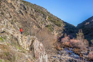 Hiker walking by Estena riverside, National Park of Cabaneros