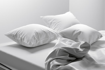 Unmade bed with soft clean white linen and pillows