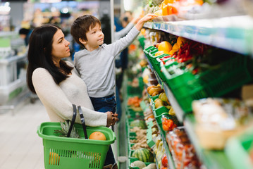 Young mother with her little baby boy at the supermarket. Healthy eating concept