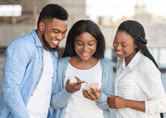 Millennial afro girl showing funny content on smartphone to friends