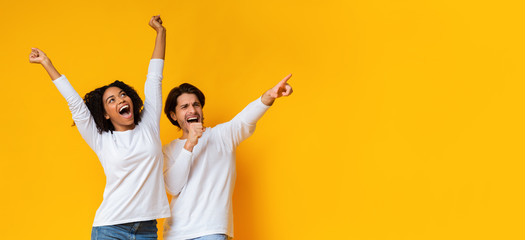 Multiracial couple dancing and singing together, having fun over yellow background Papier Peint
