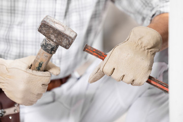 Workman or builder using a mallet and chisel
